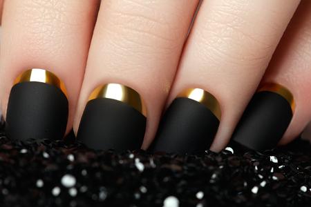 nailpolish: Manicure. Black matte nail polish. Manicured nail with black matte nail polish. Manicure with dark nailpolish. Golden nail art manicure. Holiday style bright manicure