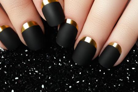 Schwarz matt Nagellack. Gepflegten Nagel mit schwarzem Mattnagellack. Maniküre mit dunklen Nagellack. Goldene Nagelkunst-Maniküre