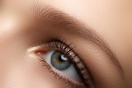 Eye makeup. Beautiful eyes make-up. Holiday makeup detail. Long eyelashes. Close-up shot of female eye make-up in smoky eyes style