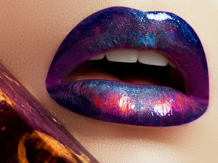 Closeup of beautiful full woman's lips with bright fashion gloss makeup. Macro shot with magenta lip make up. Beautiful lips with pink pigment. Beauty and fashion concept