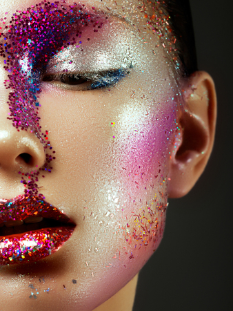 Beauty, cosmetics and makeup. Magic eyes look with bright creative make-up. Macro shot of beautiful womans face with perfect art make up with glitter. Body art