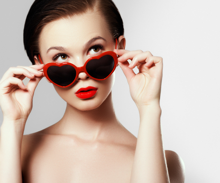 Young girl with glasses in the shape of heart. Holiday makeup. Beauty sexy lips. Valentines Day concept. Beautiful love make-up