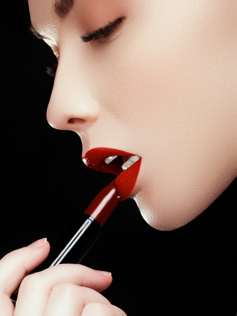 entice: Cosmetics and makeup. Perfect lip makeup. Fashion model applying lipstick. Beautiful young woman with wine lipstick. Models face with dark red colored pomade. Beauty concept