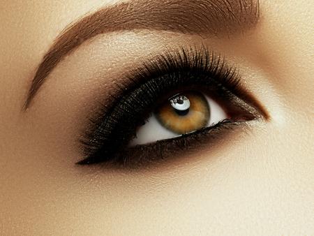 Hermoso disparo macro de ojo femenino con pestañas largas extremas y maquillaje negro de línea. Maquillaje de forma perfecta y pestañas largas. Cosméticos y maquillaje. Closeup macro disparo de la moda eyes rostro Foto de archivo - 77092651