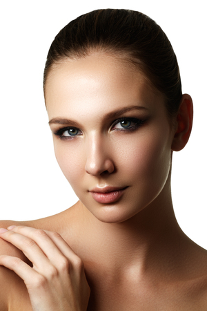 Beautiful young model with dark fashion make-up and french manicure. Purity skin. Beauty style. Fashion shiny highlighter on skin, sexy gloss lips make-up and dark eyebrows