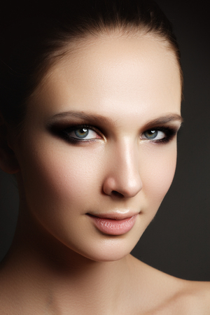Beautiful woman with bright make up eye with sexy liner makeup. Fashion big arrow shape on womans eyelid. Chic evening make-up, healthy face