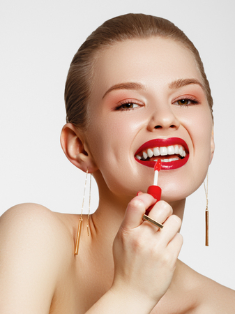 Makeup products. Young beautiful girl with gold earrings and ring smiling on white background. Red nails with manicure. A young woman with fashion accessories applying lip gloss Banco de Imagens