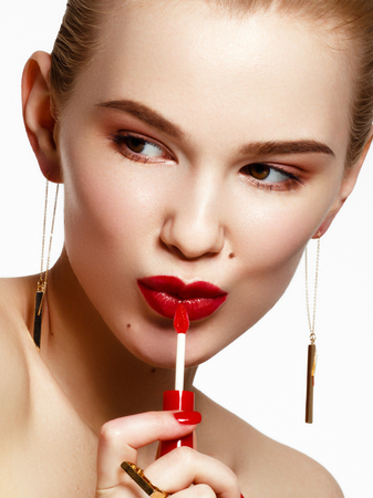 Makeup products. Young beautiful girl with gold earrings and ring smiling on white background. Red nails with manicure. A young woman with fashion accessories applying lip gloss Stock Photo