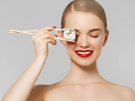 Diet and health concept. Healthy japanese food. Beautiful blonde girl with red lips and manicured nails eating sushi close-up. Smiled woman with perfect make up holding sushi roll with chopsticks