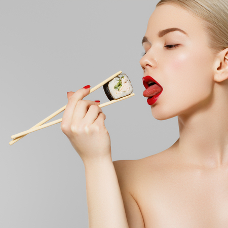 Beautiful blonde girl with red lips and manicured nails eating sushi, healthy japanese food. Beautiful woman holding chopsticks with sushi. Sexy lady