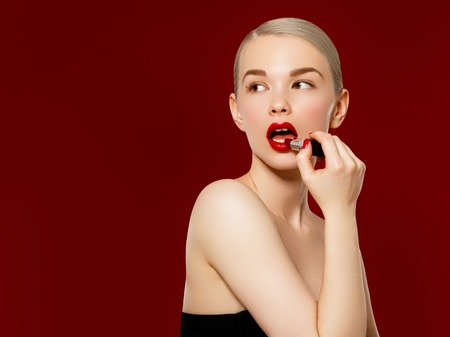 Fashion photo. Closeup of woman face with bright red matte lipstick on full lips. Beauty Cosmetics, Makeup Concept. A young girl applies makeup for lips