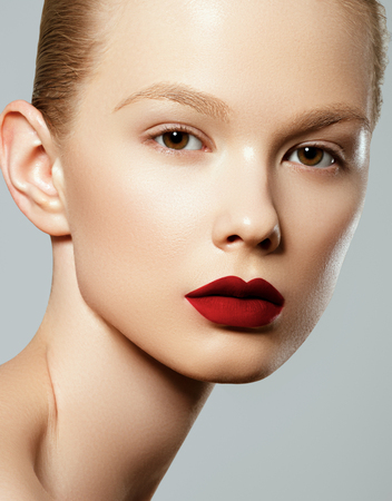 Beauty woman Face. Portrait of beautiful young female with perfect matte facial makeup. Soft healthy skin. Glamorous girl on gray background. Red lips
