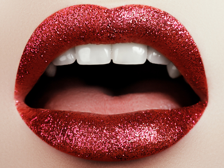 Glamour fashion bright pink lips gloss make-up with gold glitter. Macro of woman's face part. Sexy glossy lip makeup, luxury lady