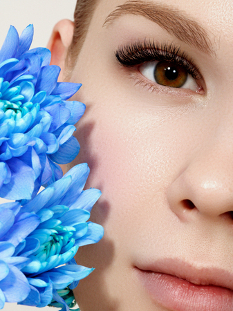 Aesthetic Cosmetology. Spring Woman. Beauty Summer model girl with colorful flowers . Beautiful Lady with Blooming flowers. Holiday Fashion Makeup. Banco de Imagens