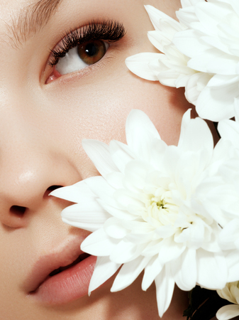 Beautiful Girl With Flowers.Beauty Model Woman Face. Perfect Skin. Professional Make-up.Makeup. Fashion Art Stock Photo