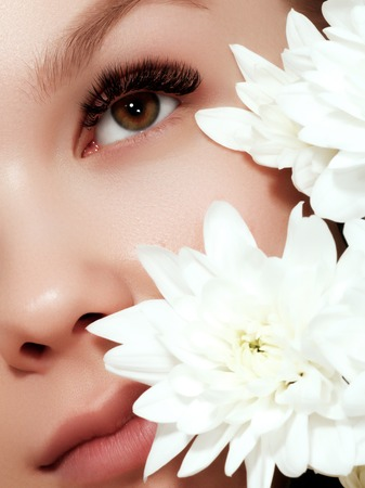 Young beauty woman with flowers closeup makeup. Cosmetics and make-up. Closeup macro shot of fashion visage