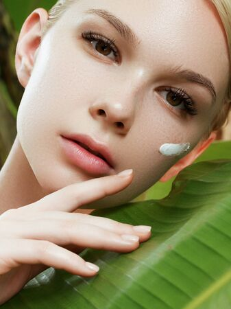 Skincare, Wellness, Spa. Clean soft Skin, healthy Fresh look. The concept of a healthy skin. Portrait of a beautiful girl against a background of tropical leaves. Spa concept. Natural beauty