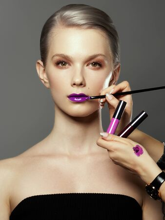 Beautiful girl surrounded by hands of makeup artists with brushes and lipstick near her face. Photo of happy woman on gray background. Grooming himself