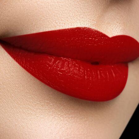 Kosmetik, Make-up und Trends. Heller Lippenstift auf den Lippen. Nahaufnahme des weiblichen Mundes der Schönheit mit rotem Lippenmake-up. Schöner Teil des weiblichen Gesichts. Perfekt saubere Haut Standard-Bild