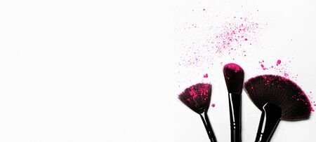Makeup brushes on white background with colorful pigment powder