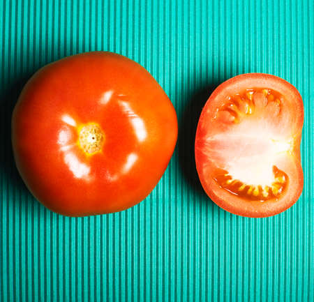 Flat lay, top view. Red ripe tomatoes on bright green background