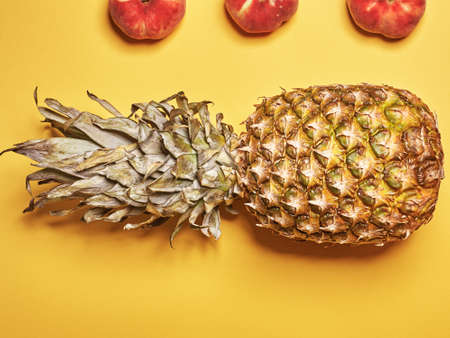 Flat lay. Top view. Peaches and pineapple on a yellow background