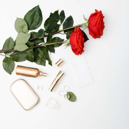 Decorative flat lay composition with cosmetics, womens accessories and flowers. Flat lay, top view on white background