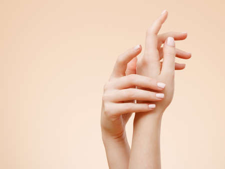 Beautiful Woman Hands. Spa and Manicure concept. Female hands with french manicure. Soft skin, skincare concept. Beauty nails. over beige background Standard-Bild