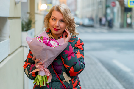 Young blonde woman with flowers bouquet on a city street at cloudy day
