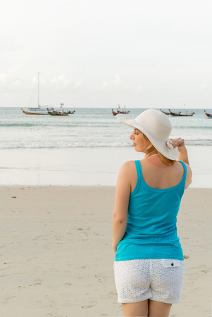 Young blonde woman on the beach in shirt and hut Stock Photo