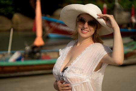 白いハットを身に着けているビキニとビーチで若いブロンドの女性のドレスします。 写真素材