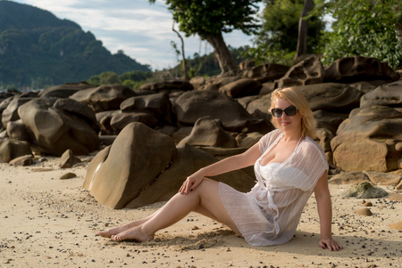 Young blonde woman on a beach in beach dress Stock Photo