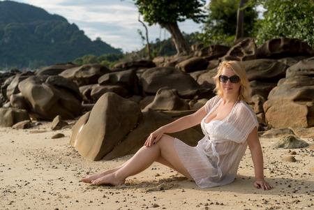 Mujer rubia joven en una playa en traje de playa Foto de archivo - 75706527