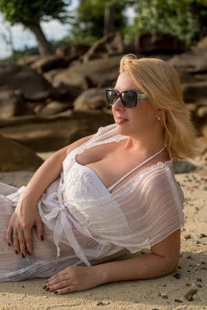 Young blonde woman on a beach in beach dress 版權商用圖片
