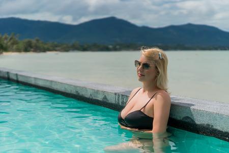 Woman relaxing in pool in resort
