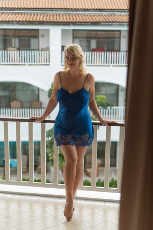 Young woman on balcony in blue lingerie