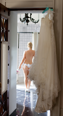 Young sexy blonde woman in bathroom dressing. Nude bride put on wedding dress