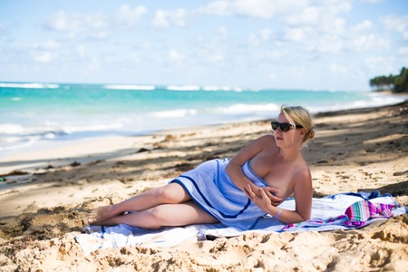 Young sexy blonde woman sunbathing near sea. Girl at the beach Stock Photo