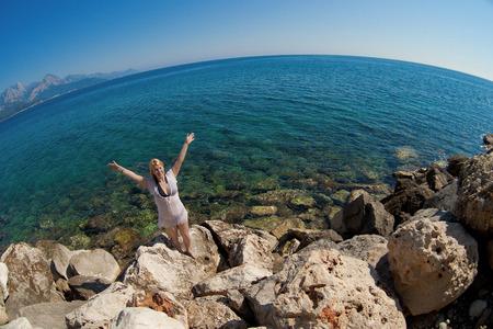 Young sexy blonde woman in bikini near sea. Girl in transparent beach dress