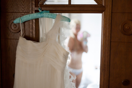 Young sexy blonde woman in bathroom dressing. Naked bride put on wedding dress
