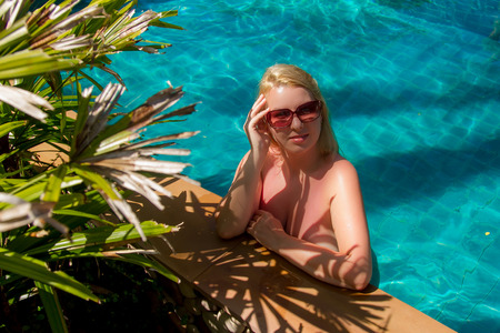 Young blonde beautiful woman in sunglasses in swimming pool bathing Reklamní fotografie - 116474267