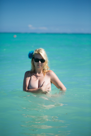 Young sexy blonde woman swimming topless in a sea. Girl at the beach vacation