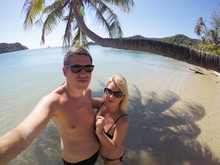 Junges Paar Sonnenbaden in einem Meer in der Nähe von Palmen am wilden Strand im Sommerurlaub