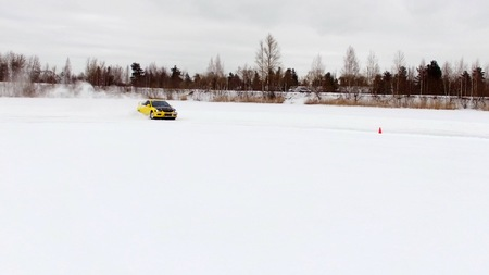 Car drives by icy track on snow covered lake at winter. Aerial view. Sport car racing on snow race track in winter. Driving a race car on a snowy road Banque d'images