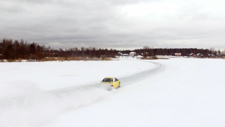 Car drives by icy track on snow covered lake at winter. Aerial view. Sport car racing on snow race track in winter. Driving a race car on a snowy road Stok Fotoğraf