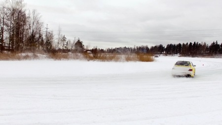 Car drives by icy track on snow covered lake at winter. Aerial view. Sport car racing on snow race track in winter. Driving a race car on a snowy road Imagens