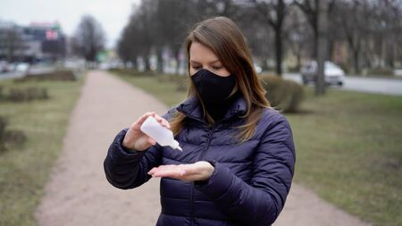 Woman in face protective mask in a city with hand sanitizer covid-19 coronavirus