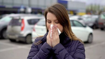 Woman blowing nose in a paper towel in a street.