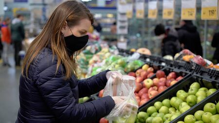 Woman in face protective mask in supermarket grocery store covid-19 coronavirus Stock fotó