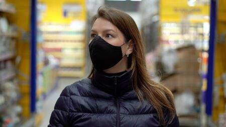 Woman in face protective mask in a supermarket shop cart at covid-19 coronavirus Stock fotó